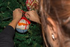 Woman`s hand fixing up some Christmas Decorations among the bran. Ches of a Christmas Tree on Blur Background royalty free stock images