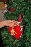 Woman`s hand fixing up some Christmas Decorations among the bran. Ches of a Christmas Tree on Blur Background royalty free stock photos