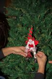 Woman`s hand fixing up some Christmas Decorations among the bran. Ches of a Christmas Tree on Blur Background stock photos
