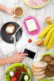 A woman's hand with food and phone Royalty Free Stock Photos