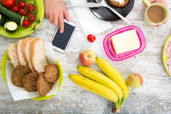 A woman's hand with food and phone Stock Image