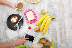A woman's hand with food and phone Stock Photography