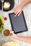 A woman's hand with food and tablet Royalty Free Stock Images