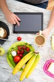 A woman`s hand with food and tablet Stock Photography