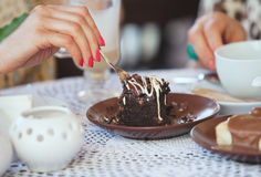 Woman's hand with a fork breaks off a piece of chocolate cake Stock Photos