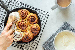 Woman`s Hand Frosting Cinnamon Rolls in Skillet Stock Photos