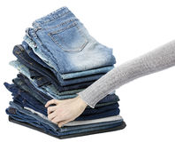 Hand Arranging Jeans Stack. Woman's hand fumbling through a stack of various pairs of jeans pants Royalty Free Stock Photo