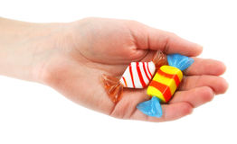 Woman's hand gives two colored candy. Isolated on a white background Royalty Free Stock Image