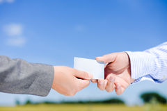 Woman's hand giving blank white business card to Royalty Free Stock Photo