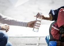Woman`s hand giving something to a homeless. Detail of woman`s hand giving a bottle of water to a homeless person stock photos