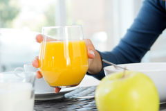 Woman's hand grabbing a glass of orange juice at breakfast Stock Photo