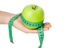 Woman's hand with green apple and tape measure Royalty Free Stock Photography