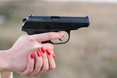 Woman's hand and a gun Stock Photo