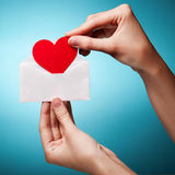 Woman's hand hold envelope with a sign of heart Stock Photo