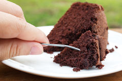Woman's hand hold a fork to slice of chocolate cake. Royalty Free Stock Photo