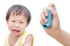 Woman's hand holding asthma inhaler foreground Stock Photo