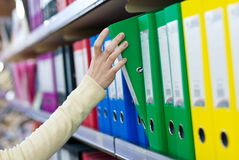 Girl's hand taking big folder from the shelves with office files. Royalty Free Stock Image