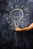 Woman's hand holding a big light bulb. Drawing on blackboard Stock Image