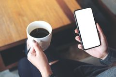 A woman`s hand holding black mobile phone with blank white desktop screen while drinking coffee in cafe. Mockup image of a woman`s hand holding black mobile Stock Image