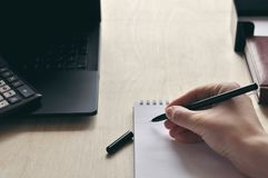A woman`s hand is holding a black pen at the Desk close-up. Study and and working concept stock images