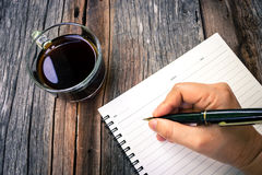 Woman's hand holding a black pen on an empty notebook. Stock Photos