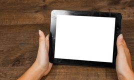 Woman`s hand holding black tablet pc with blank white screen on a wooden background. with copy space. Royalty Free Stock Images