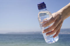 Woman's hand holding bottle of water on the beach Stock Photos