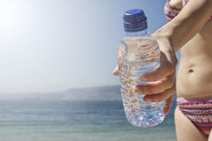 Woman's hand holding bottle of water under the sun Royalty Free Stock Photo