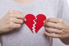 Woman`s hand is holding broken red heart. royalty free stock images
