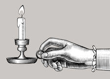 Woman`s hand holding a candlestick with burning candle. Vintage engraving stylized drawing. There is in addition a vector format EPS 8 Royalty Free Stock Photo