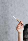 Woman's hand holding a cigarette. In a mouthpiece on grey background Stock Photo