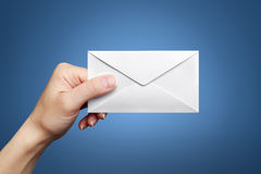 Woman's hand holding closed envelope Stock Image