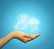 Woman's hand holding cloud sun rain icons Royalty Free Stock Photo