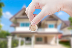 Woman's Hand holding Coin on house background,saving real estate home ownership investment. To buy as retirement income property Stock Photos