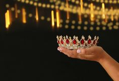 Woman& x27;s hand holding a crown for show victory or winning first place over black background with glitter overlay. Royalty Free Stock Photos