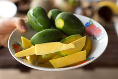 Woman`s Hand Holding Cut Green Mangos in a Bowl Royalty Free Stock Photo