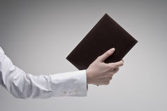 Woman's hand holding diary. Woman's hand holding brown diary with leather hardcover over light background Stock Photo