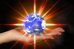 Woman's hand holding an exploding earth Royalty Free Stock Photos