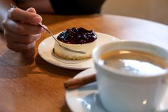 Woman`s hand holding a fork to cut a piece of blueberry cheese cake to eat with coffee cup on wooden table stock image