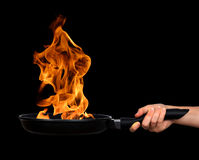Woman's hand holding a frying pan with flames. On black background Stock Photo