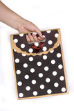 Woman's hand holding gift bag. Emale hand holding two gift paper bags black with white polka dots Royalty Free Stock Photos
