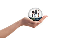 A woman's hand holding a glass ball with people inside Stock Photo