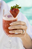 Woman's Hand Holding Glass Of Strawberry Juice Royalty Free Stock Photography