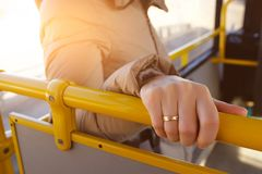Woman`s hand holding the handrail in the bus. A young girl, a passenger in public transport. The concept of urban life. Close up royalty free stock photo