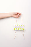 Woman's hand holding Happy Easter text decor sign Royalty Free Stock Images