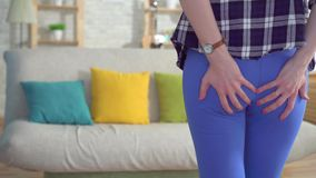 Woman`s hand holding her bottom because is pain caused by hemorrhoid. Woman with hemorrhoids and constipation stock video