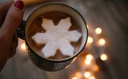 Woman`s Hand Holding Hot Cocoa with Snowflake Marshmallow stock image