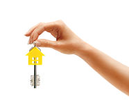 Woman's hand holding house key with keychain in the form of home Royalty Free Stock Photography