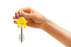 Woman's hand holding house key with keychain in the form of home Royalty Free Stock Photos