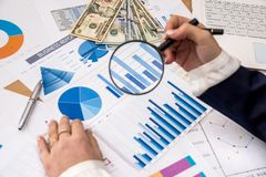 Woman`s hand holding a magnifying glass over business graph. royalty free stock image